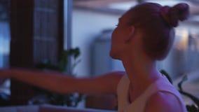 Mujer en el vestido blanco que se sienta en el sofá en partido en club nocturno holidays Cabeza de la sacudida metrajes