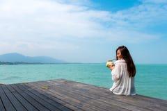 Mujer en el vestido blanco que se sienta en el jugo de consumición del coco de la terraza con el fondo del mar y del cielo azul c Fotografía de archivo libre de regalías