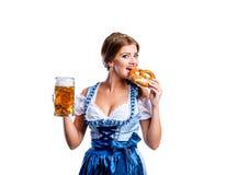 Mujer en el vestido bávaro tradicional que sostiene la cerveza y el pretzel Foto de archivo libre de regalías
