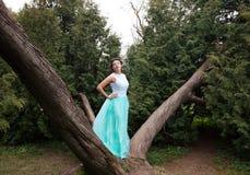 Mujer en el vestido de la elegancia que presenta en el jardín Imágenes de archivo libres de regalías