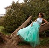 Mujer en el vestido de la elegancia que presenta en el jardín Fotografía de archivo