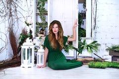 Mujer en el vestido de noche largo del verde de la moda de la belleza que se sienta en un piso Flores Imagen de archivo