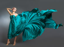 Mujer en el vestido de seda que agita en el viento Paño del vestido que vuela y que agita sobre fondo gris Imagen de archivo