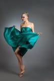 Mujer en el vestido de seda que agita en el viento Paño del vestido que vuela y que agita sobre fondo gris Fotos de archivo