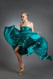 Mujer en el vestido de seda que agita en el viento Paño del vestido que vuela y que agita sobre fondo gris Foto de archivo