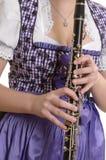 Mujer en el vestido del dirndl que juega el clarinete, detalle Imagen de archivo libre de regalías