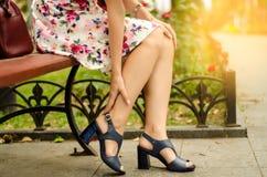 Mujer en el vestido del pie en los zapatos del dolor de la calle del banco en las piernas Fotos de archivo libres de regalías