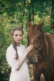 Mujer en el vestido del vintage que toca a la cara del caballo foto de archivo