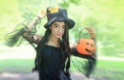 Mujer en el vestido negro y sostener la muñeca plástica de la calabaza imágenes de archivo libres de regalías