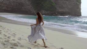 Mujer en el vestido que corre en la playa metrajes