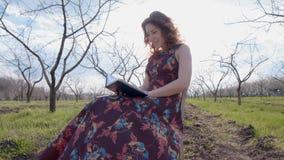 Mujer en el vestido que se sienta en el centro de Chris de la primavera almacen de metraje de vídeo