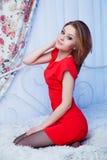 Mujer en el vestido rojo que se sienta en una cama Fotos de archivo