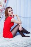 Mujer en el vestido rojo que se sienta en una cama Imagenes de archivo