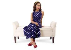 Mujer en el vestido y los muebles del vintage que parecen agujereados Foto de archivo libre de regalías