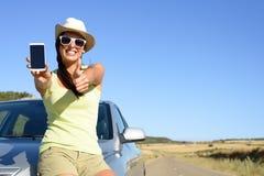Mujer en el viaje que muestra la pantalla del teléfono Imagen de archivo libre de regalías