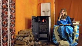 Mujer en el vino rojo de la bebida de la butaca y el libro leído cerca de la estufa rural almacen de metraje de vídeo