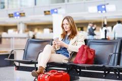 Mujer en el vuelo que espera del aeropuerto internacional para en el terminal Imágenes de archivo libres de regalías