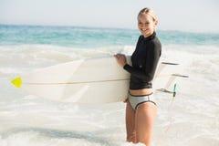 Mujer en el wetsuit que sostiene una tabla hawaiana en la playa Imagen de archivo