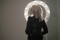 Mujer en enlace rizada que presenta, ronda ligera del pelo del maquillaje, trasera Fotografía de archivo libre de regalías