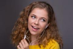 Mujer en escuchar amarillo la música en los auriculares con un alambre thr Imagen de archivo