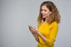 Mujer en escuchar amarillo la música en los auriculares con un alambre thr Imagen de archivo libre de regalías