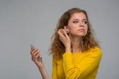 Mujer en escuchar amarillo la música en los auriculares con un alambre thr Fotografía de archivo