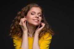 Mujer en escuchar amarillo la música en los auriculares con un alambre thr Fotografía de archivo libre de regalías