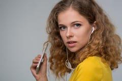 Mujer en escuchar amarillo la música en los auriculares con un alambre thr Imagenes de archivo