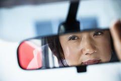 Mujer en espejo de rearview Imagen de archivo libre de regalías