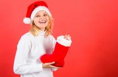 Mujer en fondo del rojo del regalo de la Navidad del control del sombrero de santa Concepto de la media de la Navidad La cara ale imagenes de archivo