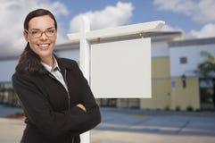 Mujer en Front Commercial Building y la muestra en blanco de Real Estate Imagenes de archivo