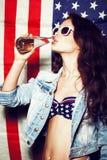 Mujer en gafas de sol con la bandera nacional de los E.E.U.U. Fotografía de archivo libre de regalías