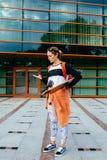 Mujer en gafas de sol con longboard y una camisa anaranjada que envía un mensaje de texto de su teléfono celular Mujer que usa el Fotos de archivo