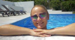 Mujer en gafas de sol que disfruta de día soleado en la piscina almacen de metraje de vídeo