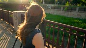 Mujer en gafas de sol que habla en el smartphone mientras que camina abajo de la calle en la puesta del sol, cierre para arriba,  metrajes