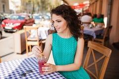 Mujer en gafas de sol redondas con el cóctel en la terraza del café que se divierte Foto de archivo libre de regalías
