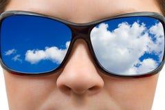 Mujer en gafas de sol y la reflexión del cielo Foto de archivo