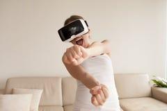 Mujer en gafas de VR que disfruta del juego 3d en casa Imagen de archivo libre de regalías