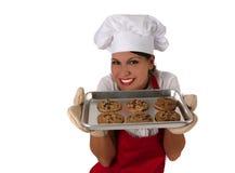 Mujer en galletas de la hornada del delantal Imágenes de archivo libres de regalías