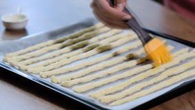 Mujer en grissini del cepillo de la cocina con aceite de oliva Cocinar grissini italiano metrajes