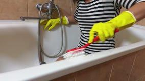 Mujer en guantes amarillos con el baño limpio del cepillo rojo almacen de video