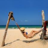 Mujer en hamaca en la playa imagen de archivo