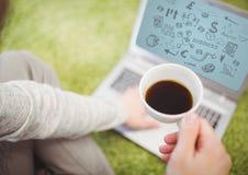 Mujer en hierba con el café y el ordenador portátil que muestran garabatos negros del negocio y el fondo azul Imagen de archivo