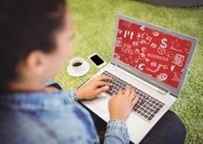 Mujer en hierba con el ordenador portátil que muestra los garabatos blancos del negocio y el fondo rojo Foto de archivo