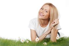 Mujer en hierba con las flores Fotos de archivo libres de regalías