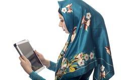 Mujer en Hijab usando una tableta imagen de archivo libre de regalías
