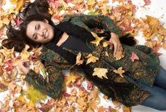 Mujer en hojas Imagen de archivo libre de regalías