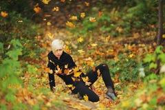 Mujer en hojas caidas tiros del parque del otoño Imagen de archivo libre de regalías