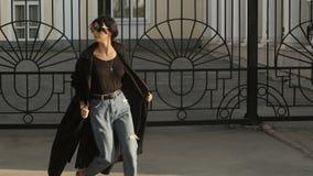 Mujer en impermeable que camina cerca de la puerta almacen de video