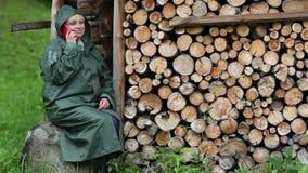 Mujer en impermeable verde con el teléfono móvil rojo almacen de video